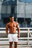 Gorący Piękny czarny facet z wyłupiastymi mięśniami pozuje przeciw tłu miastowy krajobraz Mężczyzna sprawności fizycznej model Obraz Stock