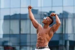 Gorący Piękny czarny facet z wyłupiastymi mięśniami pozuje przeciw tłu miastowy krajobraz Mężczyzna sprawności fizycznej model Obrazy Royalty Free