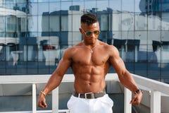 Gorący Piękny czarny facet z wyłupiastymi mięśniami pozuje przeciw tłu miastowy krajobraz Mężczyzna sprawności fizycznej model z  Obraz Stock