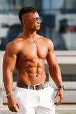 Gorący Piękny czarny facet z wyłupiastymi mięśniami pozuje przeciw tłu miastowy krajobraz Mężczyzna sprawności fizycznej model Zdjęcie Royalty Free
