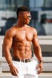 Gorący Piękny czarny facet z wyłupiastymi mięśniami pozuje przeciw tłu miastowy krajobraz Mężczyzna sprawności fizycznej model z  Fotografia Royalty Free