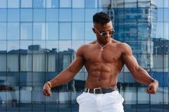 Gorący Piękny czarny facet z wyłupiastymi mięśniami pozuje przeciw tłu miastowy krajobraz Mężczyzna sprawności fizycznej model Zdjęcia Stock