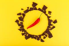Gorący pieprz w okręgu łamana czekolada na żółtym tle Fotografia Royalty Free