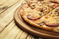 Gorący pizza plasterek z roztapiającym serem na nieociosanym drewnianym stole animusz zdjęcia stock