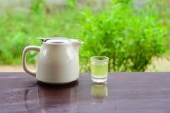 Gorący zielona herbata garnek, szkło na drewno stole i Fotografia Stock