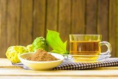 Gorący ziołowy noni, Noni ziołowy sok z noni owoc i noni proszek na drewnianym tle, fotografia stock