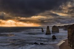 GOR 7 Apostles Storm. Stormy dark weather at sunset over famouse twelve apostles limestone rocks in marina park of Great Ocean road in Victoria towards setting Royalty Free Stock Photo