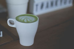 Gorąca zielonej herbaty latte sztuka na drewnianym stole Fotografia Royalty Free