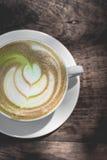 Gorąca zielonej herbaty latte sztuka na drewnianym stole Obrazy Stock