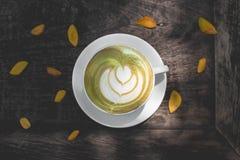 Gorąca zielonej herbaty latte sztuka na drewnianym stole Obraz Royalty Free