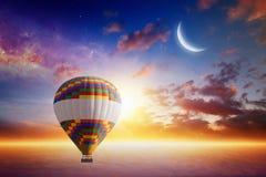 Gorące powietrze balon wzrasta bardzo wysoko w zmierzchu niebie nad rozjarzony clou Obraz Royalty Free
