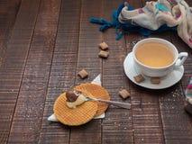 Gorący zielonej herbaty i cukierki gofry z sztywniakiem na drewnianym stole Obrazy Royalty Free