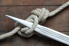 Gordian Knot. Closeup of dagger and rope tied knot on wooden background Royalty Free Stock Photos
