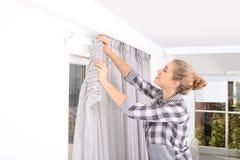 Gordijn van het vrouwen het hangende venster binnen Binnenlands decor stock foto