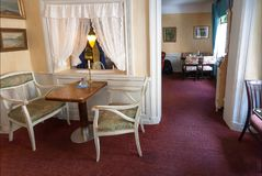 Gordijnen en retro leunstoelen zonder bezoekers in klassieke binnenlandse koffie binnen oud huis Stock Fotografie