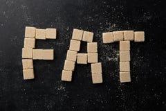 A gordura da palavra feita de cubos do açúcar Imagens de Stock Royalty Free