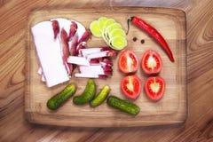 Gordura salgado crua da carne de porco com vegetais em uma placa de madeira Foto de Stock Royalty Free