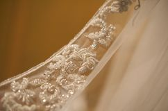 Goregous beaded hem of a bridal gown. A close up image of a gorgeous beaded lace hem on a bridal gown royalty free stock image