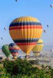 Goreme,卡帕多细亚,土耳其- 2018年6月10日, :五颜六色的热空气看法迅速增加飞行在日出的红色谷 免版税库存图片