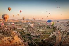 Goreme, Cappadocia, Турция - 10-ое июня 2018: взгляд красочных горячих воздушных шаров летая над красной долиной на восходе солнц Стоковые Фото