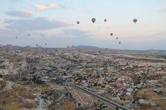 Goreme, Cappadocia, Turquia - 16 de agosto de 2017: Vista bonita da vila de Goreme com os balões que voam sobre ela no nascer do  Imagem de Stock