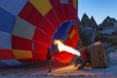 Goreme, Turkey / April 6, 2016 - Pilot fires the heater in his hot air balloon. As he prepares it for flight royalty free stock image