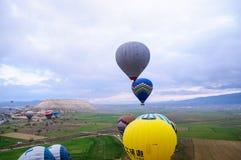 GOREME, TURKIJE - APRIL 10: Hete luchtimpulsen alvorens te vliegen en vlieg royalty-vrije stock afbeeldingen