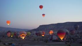 GOREME, TURQUIE - 1ER NOVEMBRE 2018 : les llots des ballons colorés commencent à voler au-dessus de la vallée au crépuscule de pr banque de vidéos
