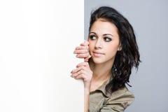 Gorgeosu young brunette with blank billboard. Stock Image
