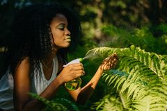 The gorgeours young charming african girl with green eye shadows and lipstick spraying the ferns using the green plastic Stock Photos