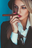 Gorgeous adult blonde woman smoking cigar Royalty Free Stock Image
