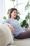 Gorgeous adult woman sitting on sofa in bright living room Royalty Free Stock Photos