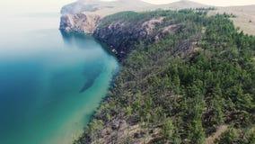 Gorgeous 4k aerial drone seascape panorama of Lake Baikal Siberia Russia stone mountain cliff pine tree canyon desert. Gorgeous aerial drone seascape panorama of stock footage