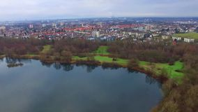 Gorgeous aerial 4k drone flight over calm small city cityscape with big mirror surface lake in park on cloudy day. Fascinating aerial 4k drone flight over calm stock footage