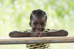 Gorgeous African girl looking at camera. Little african girl sitting at wooden table and smiling at camera with blurred background Stock Photos