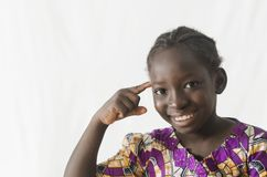Gorgeous African girl pointing finger at her head, isolated on w. Beautiful shot of African children taken in a studio in Bamako, Mali Royalty Free Stock Photography