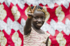 Gorgeous African girl posing with fingers as a peace sign. Young african girl with traditional accessories in hair doing victory sign and looking at camera Stock Image