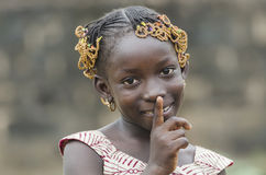 Gorgeous African school girl posing with finger on mouth. Young african girl with traditional accessories in hair looking at camera Royalty Free Stock Photography