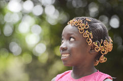 Gorgeous African School girl side view outdoors. Side view portrait of young african girl with traditional accessories in hair with blurred background Royalty Free Stock Photos