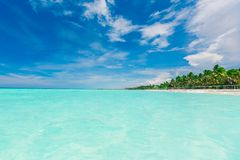 Gorgeous amazing view of deep blue sky and tranquil turquoise ocean merging together on horizon line with tropical beach. Stunning gorgeous amazing view of deep Royalty Free Stock Image