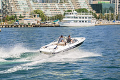 Gorgeous amazing view of people driving motor boat on the lake Ontario at high speed Royalty Free Stock Image