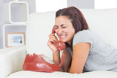 Gorgeous amused woman using a dial phone Royalty Free Stock Photos