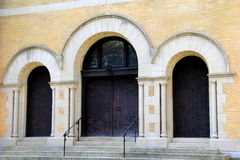 Gorgeous architecture in stone church and three heavy doors Royalty Free Stock Photo