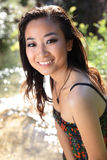 Gorgeous asian/chinese girl smiling. While outdoors near a river Royalty Free Stock Images