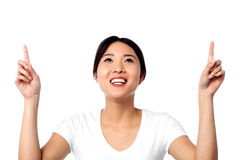 Gorgeous asian girl pointing upwards Royalty Free Stock Images