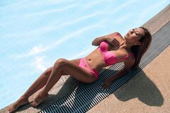 Free Gorgeous Asian Woman In A Pink Bikini Lying By The Crystal Clear Pool During Her Awesome Vacation In Luxury Hotel Resort Stock Photography - 190471622