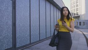 Asian office worker using phone, drinking coffee. Gorgeous asian young female office worker having lunch break, walking with coffee to go and cellphone in hand stock footage