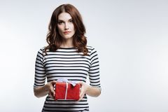 Gorgeous auburn-haired woman holding a gift box Royalty Free Stock Photography