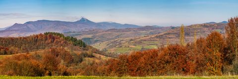 Gorgeous autumn countryside panorama in mountains. Forest with red foliage on rolling hills, village in valley and mountain ridge with high peak in a distance Royalty Free Stock Image