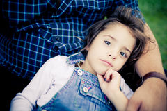 Gorgeous baby girl relaxing in father's lap Royalty Free Stock Photography